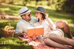Pares que gozan del libro de lectura al aire libre del tiempo de la comida campestre foto de archivo libre de regalías