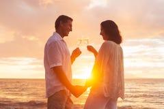 Pares que gozan del vidrio de Champene en la playa en la puesta del sol Foto de archivo libre de regalías