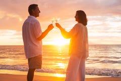 Pares que gozan del vidrio de Champene en la playa en la puesta del sol Fotos de archivo
