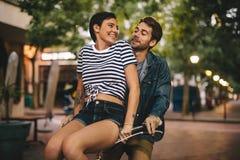 Pares que gozan en la bicicleta en la ciudad foto de archivo
