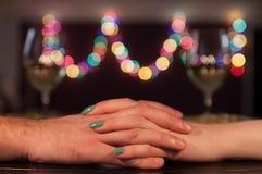 Pares que guardam as mãos durante o jantar romântico Fotografia de Stock