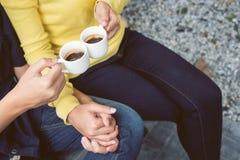 Pares que guardam as mãos e que bebem o café no jardim fotografia de stock royalty free