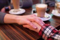 Pares que guardam as mãos no café Imagens de Stock