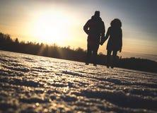 Pares que guardam as mãos no por do sol do inverno fotos de stock