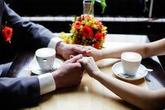 Pares que guardam as mãos no restaurante Fotos de Stock Royalty Free