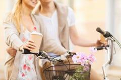 Pares que guardam o café e que montam a bicicleta Fotografia de Stock Royalty Free