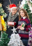 Pares que guardam presentes de Natal na loja fotos de stock royalty free