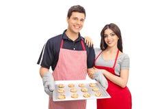 Pares que guardam uma bandeja com cookies dos pedaços de chocolate Imagens de Stock Royalty Free