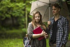 Pares que hablan al aire libre Muchacha con un libro rojo en sus manos y el individuo con el paraguas Foto de archivo libre de regalías
