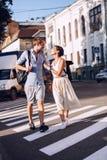 Pares que hablan en paso de peatones en la puesta del sol Imágenes de archivo libres de regalías