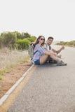 Pares que hacen autostop en el camino del campo Fotos de archivo libres de regalías