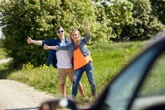 Pares que hacen autostop y que paran el coche en campo Fotografía de archivo libre de regalías