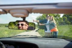 Pares que hacen autostop y que paran el coche en campo Imágenes de archivo libres de regalías