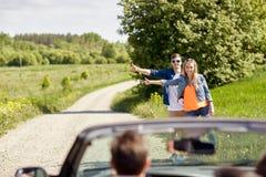 Pares que hacen autostop y que paran el coche en campo Fotos de archivo libres de regalías