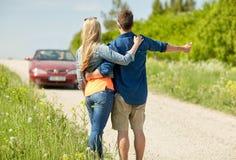 Pares que hacen autostop y que paran el coche en campo Foto de archivo libre de regalías