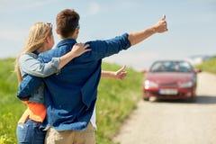 Pares que hacen autostop y que paran el coche en campo Imagen de archivo