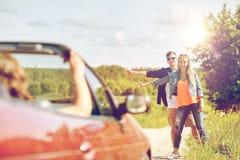 Pares que hacen autostop y que paran el coche en campo Fotografía de archivo