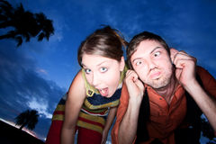 Pares que hacen caras divertidas en la puesta del sol Imagen de archivo libre de regalías