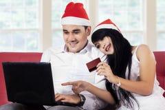 Pares que hacen compras en línea en día de fiesta de la Navidad Foto de archivo