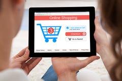 Pares que hacen compras en línea en la tableta de Digitaces Foto de archivo libre de regalías
