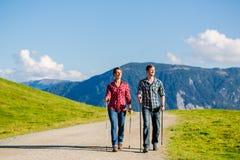 Pares que hacen ejercicio que camina del nordic en montañas Foto de archivo