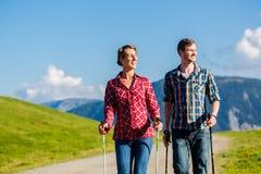 Pares que hacen ejercicio que camina del nordic en montañas Fotos de archivo