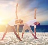 Pares que hacen ejercicios de la yoga en la playa Imagen de archivo