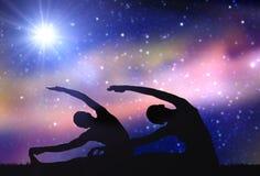 Pares que hacen ejercicios de la yoga sobre fondo del espacio Imagen de archivo libre de regalías