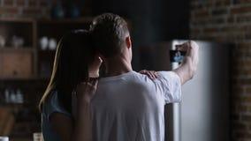 Pares que hacen el autorretrato en el teléfono elegante en casa metrajes