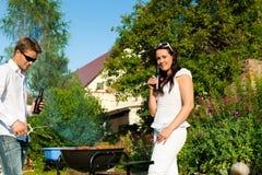 Pares que hacen el Bbq en jardín en verano Imágenes de archivo libres de regalías