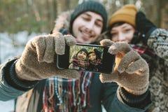 Pares que hacen el selfie en bosque del invierno Foto de archivo libre de regalías