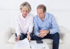 Pares que hacen finanzas de la familia en casa imagen de archivo