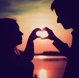 Pares que hacen forma del corazón con sus manos en orilla del lago Imagen de archivo libre de regalías