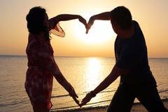 Pares que hacen forma romántica del corazón en la salida del sol Imagen de archivo