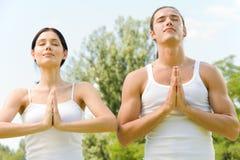 Pares que hacen movimientos de la yoga Foto de archivo libre de regalías
