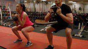Pares que hacen posiciones en cuclillas cargadas en gimnasio metrajes