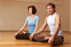Pares que hacen práctica de la yoga Imagen de archivo
