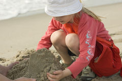 Pares que hacen un castillo de la arena Fotografía de archivo