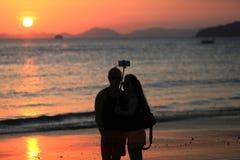 Pares que hacen una pausa el mar en la puesta del sol Fotografía de archivo