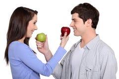 Pares que intercambian manzanas Fotos de archivo