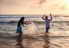 Pares que jogam no oceano imagens de stock royalty free