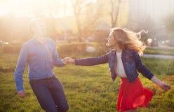 Pares que jogam no parque no por do sol Imagem de Stock Royalty Free