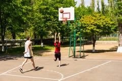 Pares que jogam o basquetebol na corte exterior Imagens de Stock