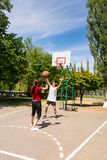 Pares que jogam o basquetebol na corte exterior Fotografia de Stock Royalty Free