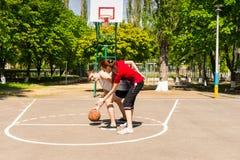 Pares que jogam o basquetebol na corte exterior Fotos de Stock Royalty Free
