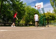 Pares que jogam o basquetebol na corte exterior Imagem de Stock