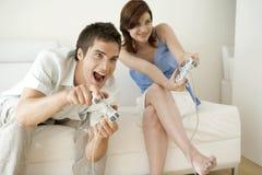 Pares que jogam os jogos video em casa Fotografia de Stock