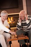 Pares que juegan a ajedrez en sala de estar acogedora Fotografía de archivo