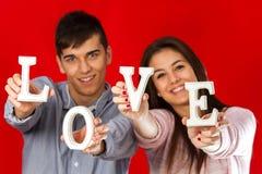 Pares que juegan con las letras de molde del amor. Foto de archivo libre de regalías