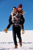 Pares que juegan en nieve Hombre que da paseo del transporte por ferrocarril de la mujer el vacaciones del invierno Imagen de archivo
